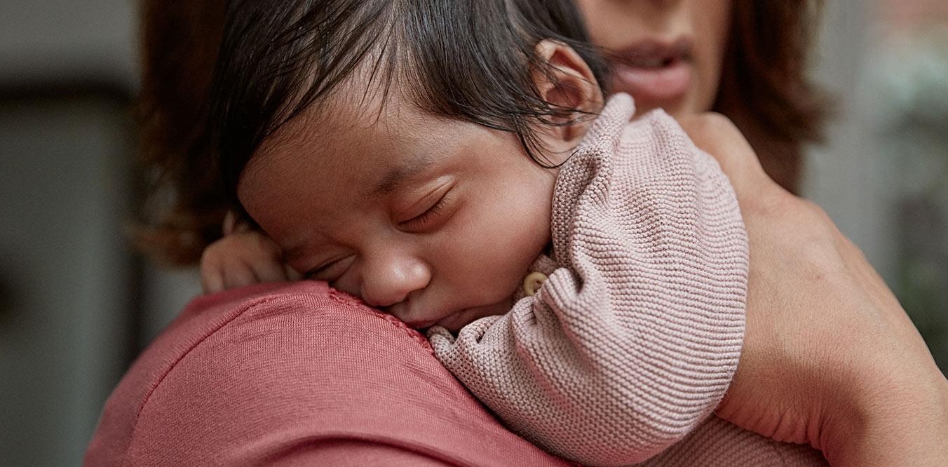newborn sleeping on parent image
